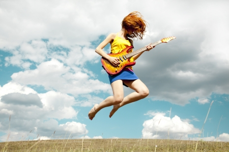 Redhead girl jumping with guitar at outdoor. photo