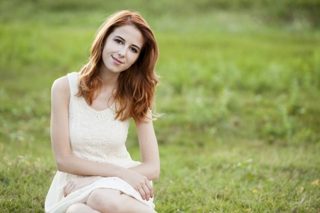 Redhead girl at green grass at village outdoor. photo