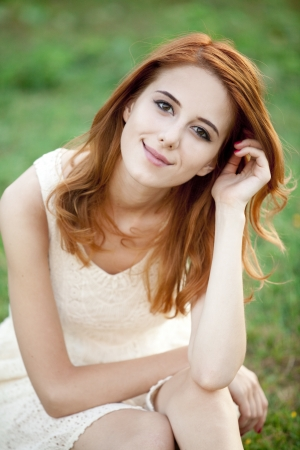 country girls: Redhead girl at green grass at village outdoor. Stock Photo