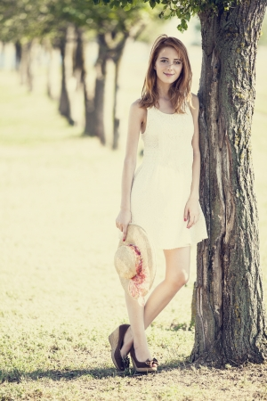 Redhead girl with hat near tree. photo