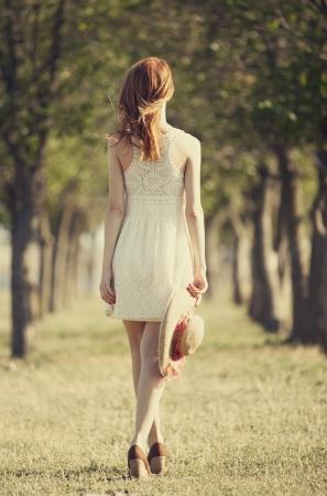 enchantress: Redhead girl at trees alley.