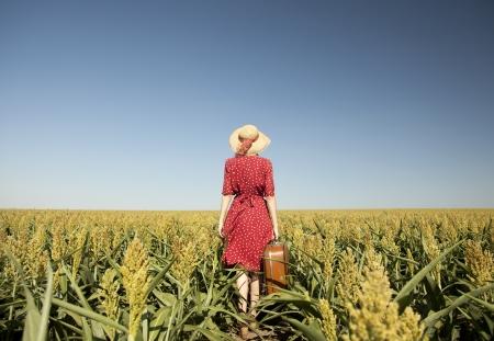 femme avec valise: Redhead girl avec une valise au champ de ma�s.