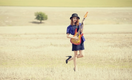 Style redhead girl with guitar at outdoor. photo