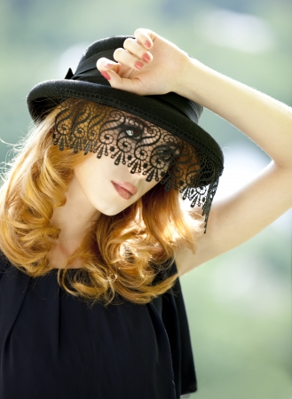 hat with feather: Fashion redhead girl with vail.