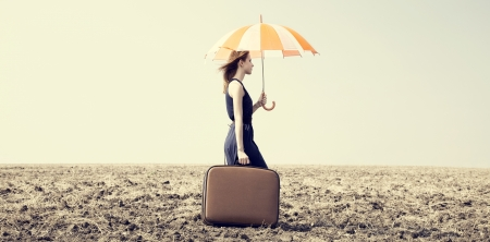 Redhead girl with umbrella and suitcase at windy grass meadow. photo