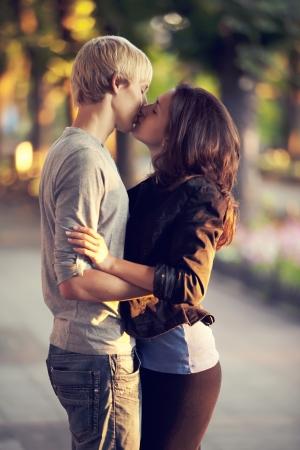 pareja de adolescentes: Joven pareja bes�ndose en la calle