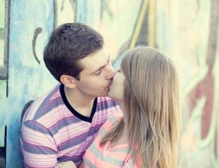 novios besandose: Joven pareja bes�ndose cerca de graffiti de fondo. Foto de archivo
