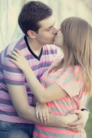 baiser amoureux: Jeune couple baisant pr�s de fond graffiti.