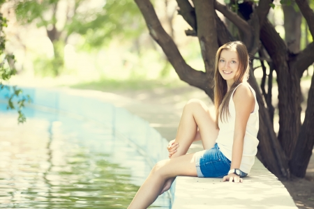 free image: Teen girl near lake in the park.