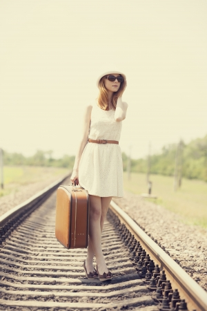 Young fashion girl with suitcase at railways. photo