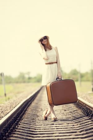 maletas de viaje: Chica de moda joven con la maleta en los ferrocarriles. Foto de archivo