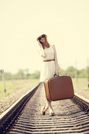 fashion girl: Young fashion girl with suitcase at railways.