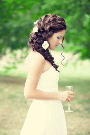 Sad bride with champagne glass photo