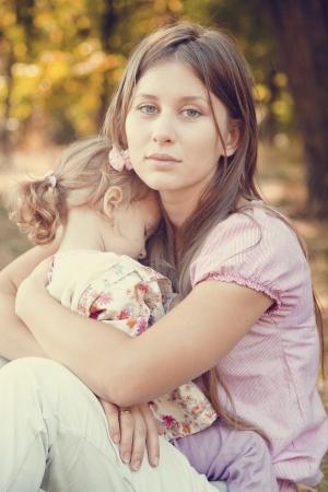mujeres tristes: Triste niña pequeña y su madre en el parque Foto de archivo