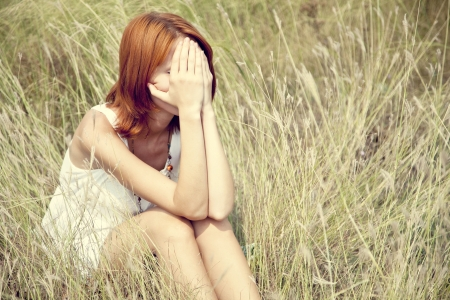 the sad girl: Sad red-haired girl at grass. Outdoor photo.