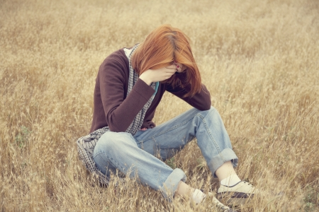 Lonely sad red-haired girl at field Stock Photo - 14961551