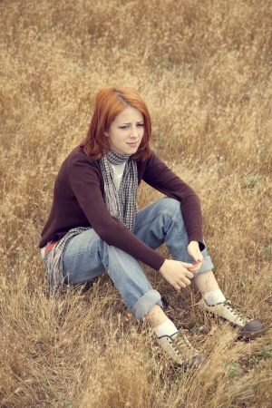 Lonely sad red-haired girl at field Stock Photo - 14961587