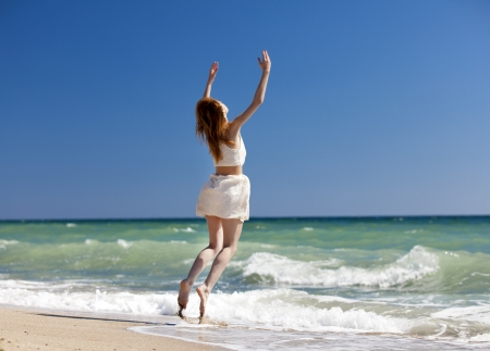 Young redhead girl jumping at the beach. photo