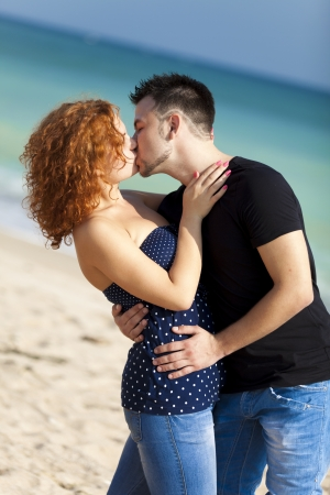 Young couple kissing at the beach  photo