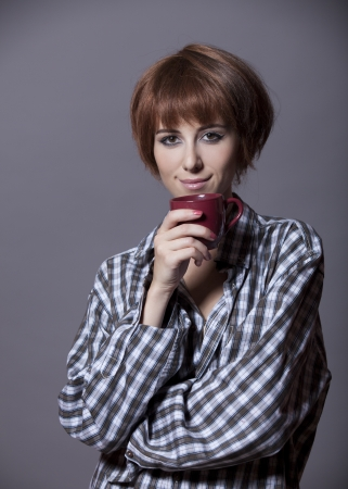 Style girl in shirt with cup at studio. Stock Photo - 15643357