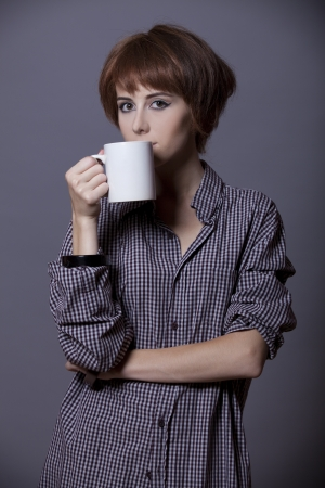 Style girl in shirt with cup at studio. photo