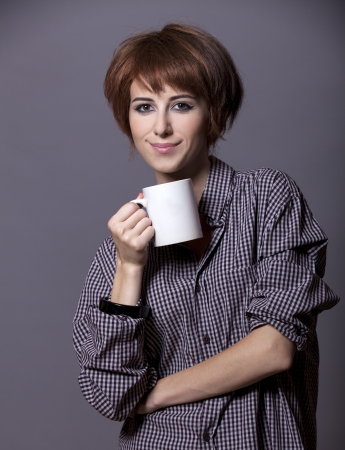 Style girl in shirt with cup at studio. Stock Photo - 15643347