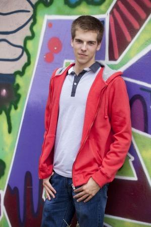 Style teen standing near graffiti wall. photo