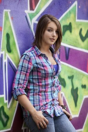 graffiti brown: Estilo de pie muchacha adolescente cerca de la pared de graffiti. Foto de archivo