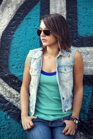 woman street: Teen girl in sunglasses near graffiti wall.