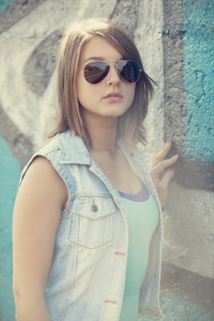 graffiti brown: Muchacha adolescente en gafas de sol cerca de la pared de graffiti.