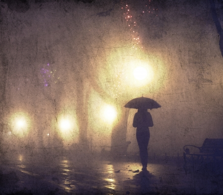 alone in the dark: Single girl with umbrella at night alley Stock Photo