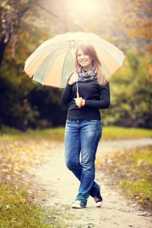Beautiful girl with umbrella at autumn park. photo