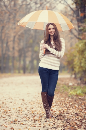 Beautiful girl with umbrella at autumn park. photo