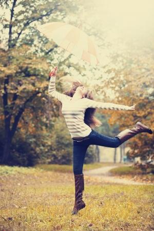 Beautiful girl with umbrella at autumn park.