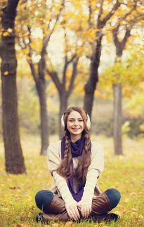 Young fashion girl with headphones at autumn park. photo