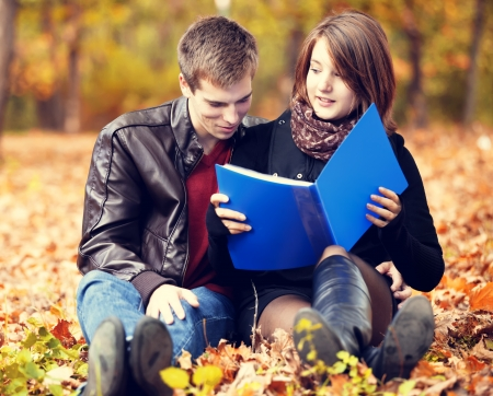 Beautiful couple with notebook at autumn park. photo