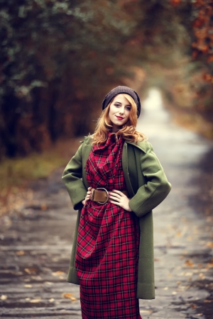the enchantress: Style redhead girl at beautiful autumn alley. Stock Photo