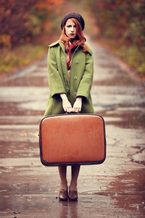 Style redhead girl with suitcase at beautiful autumn alley. photo