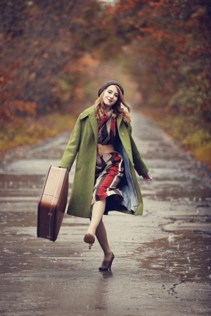 the enchantress: Style redhead girl with suitcase at beautiful autumn alley.