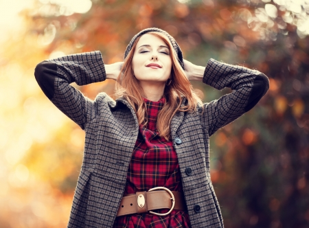 woman fashion: Style redhead girl at beautiful autumn alley. Stock Photo