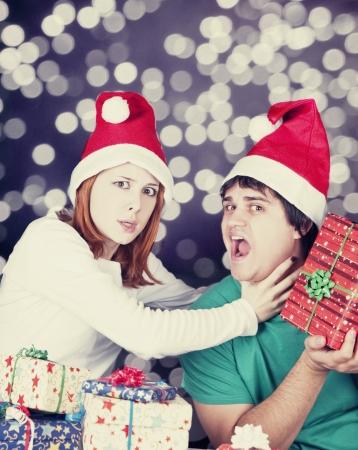 strangling: Girl strangling her boyfriend for a christmas gift. Studio shot.