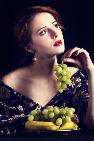Portrait of beautiful rich women with grapes. photo