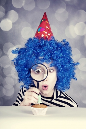 comically: Funny girl with blue hair and striped knitted jacket looking through loupe at cake for birthday with one candle.