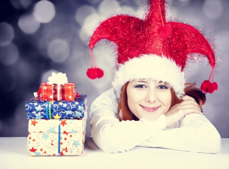 Funny red-haired girl in christmas cap with gift boxes. Stock Photo - 16304839