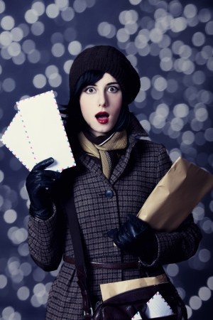 Young surprised postman girl with mail. Photo in old color style with bokeh. photo