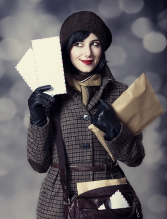 Young postman girl with mail. Photo in old color style with bokeh. photo