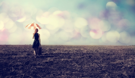 Redhead girl with umbrella and suitcase at windy field photo