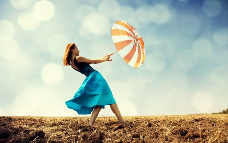 Redhead girl with umbrella at windy field. Stock Photo - 16591846