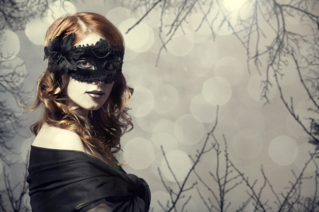 Beautiful women in carnival mask. Photo with forest at background.