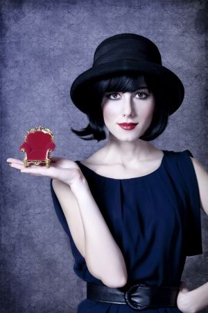 Style girl in hat holding toy armchair. photo